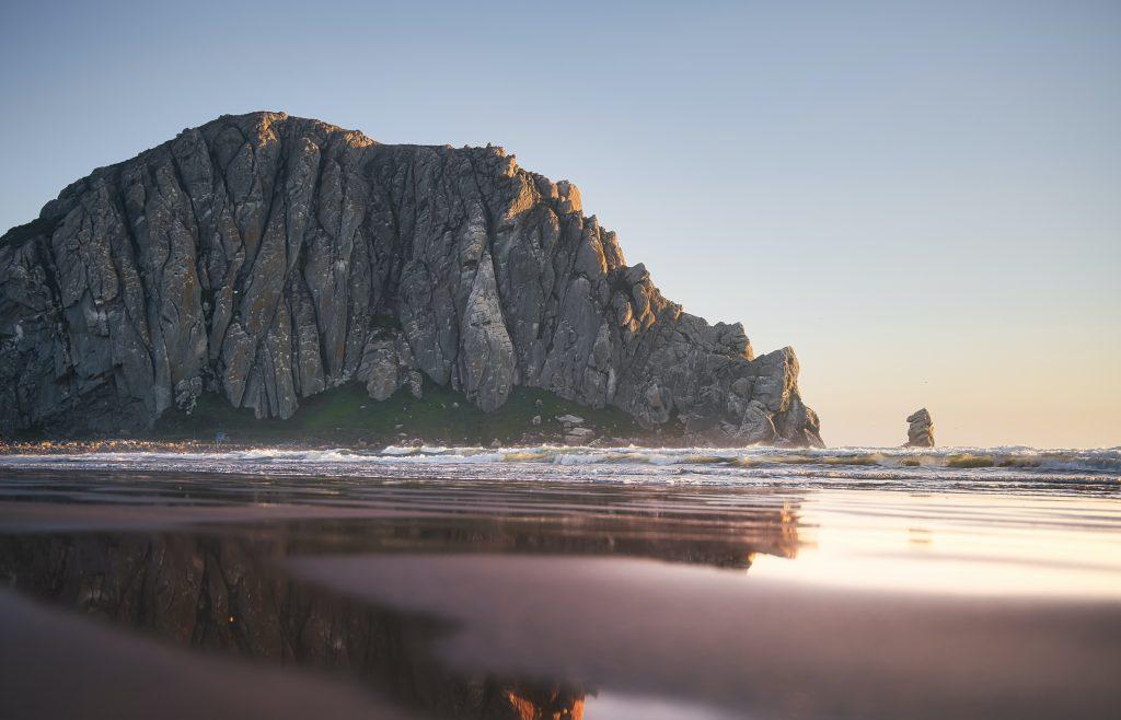 view point from the beach looking out to morro rock landmark in the ocean off the coast and the sun setting, things to do in morro bay