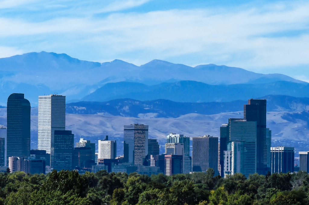 Things to do in Denver, photo of denver skyline with blue mountains and sky behind it